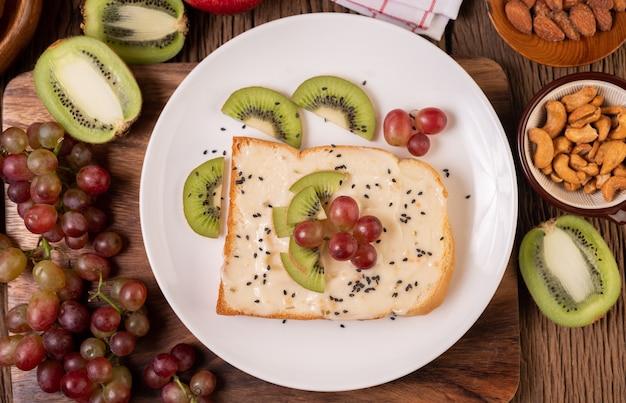 Das brot mit marmelade bestreichen und mit kiwi und trauben auf einen weißen teller legen