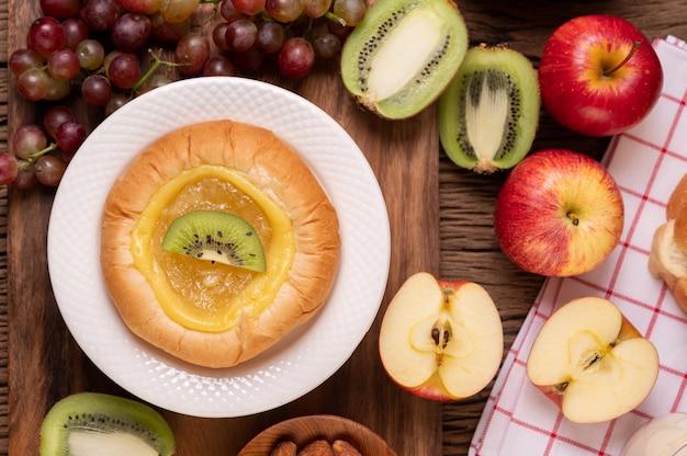 Das brot mit marmelade bestreichen und mit kiwi und trauben belegen