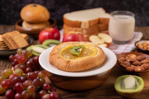 Das brot mit marmelade bestreichen und mit kiwi und trauben den apfel auf den holztisch legen