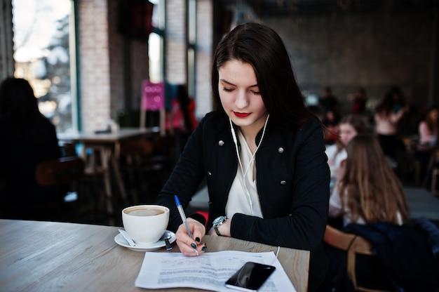Das brunettemädchen, das auf café mit schale cappuccino, hörende musik auf kopfhörern sitzt und schreiben einige dokumente.