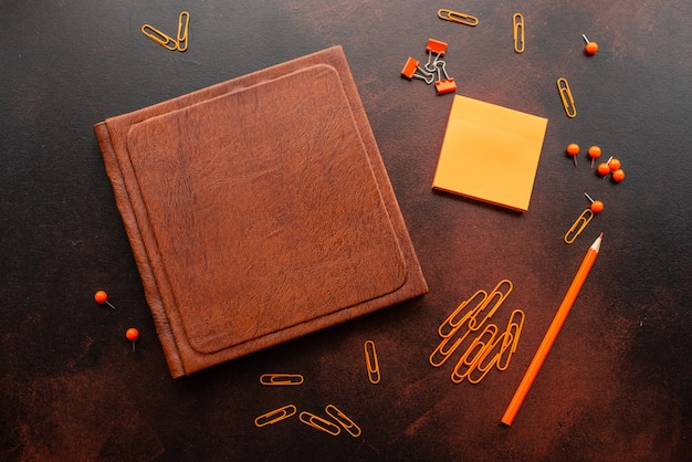 Das buch, der bleistift, die büroklammern und die markierungsblätter liegen auf einem schreibtisch