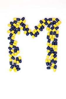 Das buchstabe m-alphabet gemacht von den medizinischen kapseln