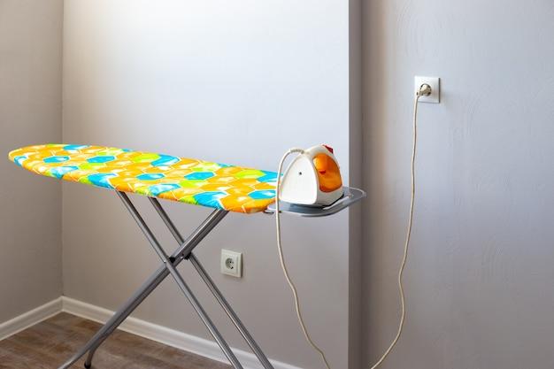 Das bügeleisen auf dem bügelbrett wird in die steckdose gesteckt. sicheres bügeln, smart home.