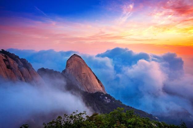 Das bukhansan-gebirge ist im bukhansan-nationalpark in seoul in südkorea von morgennebel und sonnenaufgang bedeckt.