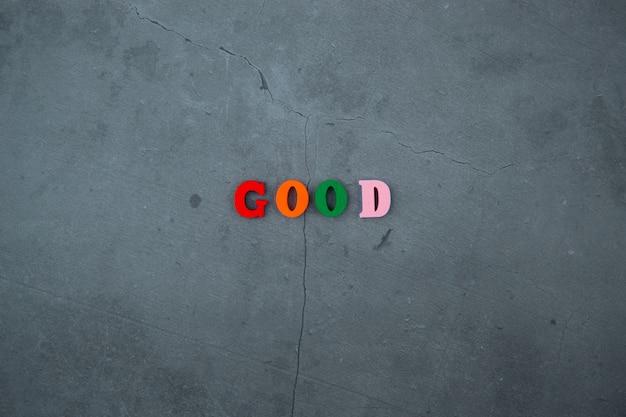 Das bunte gute wort besteht aus holzbuchstaben an einer grau verputzten wand.