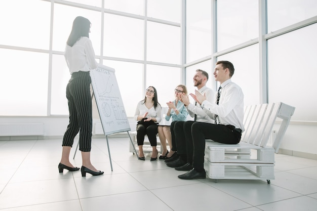 Das business-team begrüßt die geschäftsfrau bei der präsentation des neuen projekts
