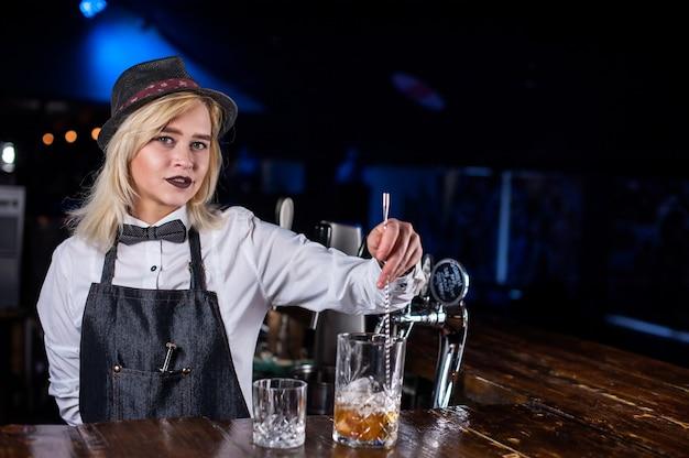 Das charmante barkeeper-mädchen gießt im nachtclub einen drink ein