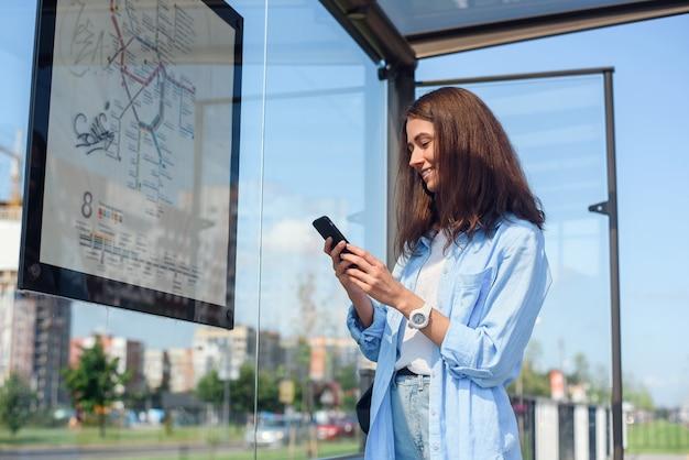 Das charmante junge mädchen überwacht den bus über eine mobile app, während es morgens an einer haltestelle der öffentlichen verkehrsmittel steht.
