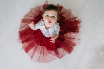 Das charmante Kind sitzt auf dem Boden