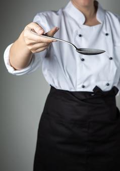Das chefhandlöffelkochen bereiten lebensmittel im küchenrestaurant zu, damit sie köstlich schmecken