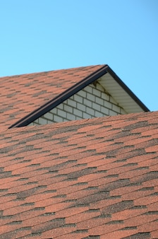 Das dach ist mit braunen bitumenschindeln bedeckt. qualität dachdecker