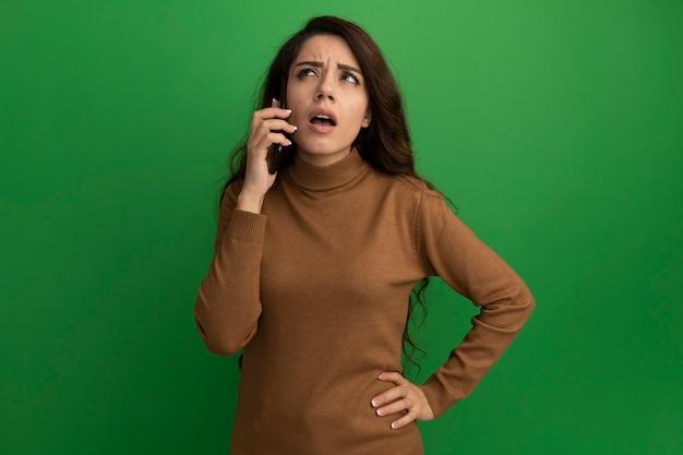 Das denken, das junges schönes mädchen nach oben schaut, spricht am telefon, das hand auf hüfte lokalisiert auf grüner wand setzt