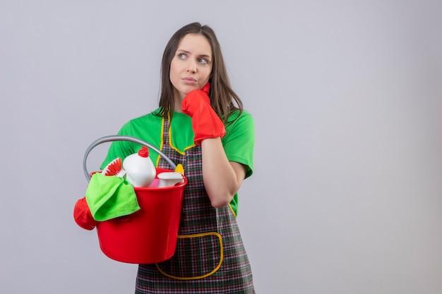 Das denken des reinigens des jungen mädchens, das uniform in den roten handschuhen hält, die reinigungswerkzeuge halten, legte ihre hand auf wange auf isolierte weiße wand