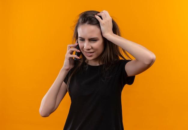 Das denkende junge kaukasische mädchen, das schwarzes t-shirt trägt, spricht am telefon, legte ihre hand auf kopf auf isolierte orange wand