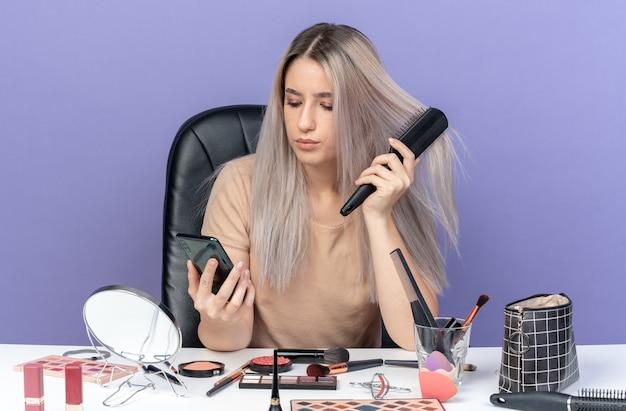 Das denkende junge schöne mädchen sitzt am tisch mit make-up-werkzeugen, die haare kämmen und das telefon einzeln auf blauem hintergrund betrachten