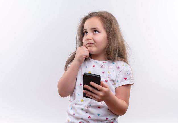 Das denkende kleine schulmädchen, das weißes t-shirt hält, das telefon hält, legte ihre hand auf wange auf isolierte weiße wand