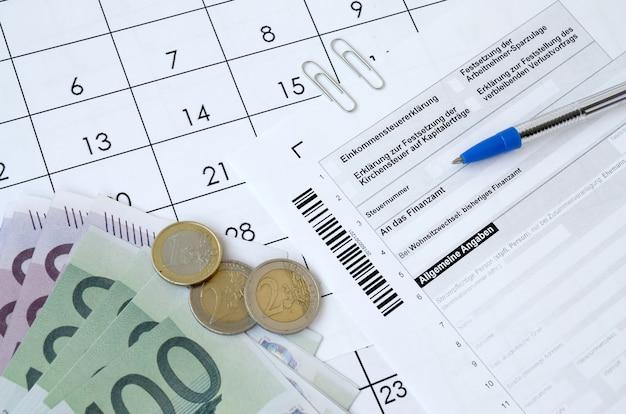 Das deutsche steuerformular mit stift und europäischen geldscheinen liegt auf dem bürokalender. steuerzahler in deutschland verwenden euro-währung, um steuern zu zahlen