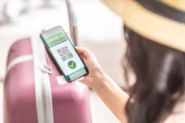 Das digitale grüne zertifikat für internationale reisen zeigt eine grüne covid-19-geimpfte zecke und einen qr-code im smartphone einer frau an.