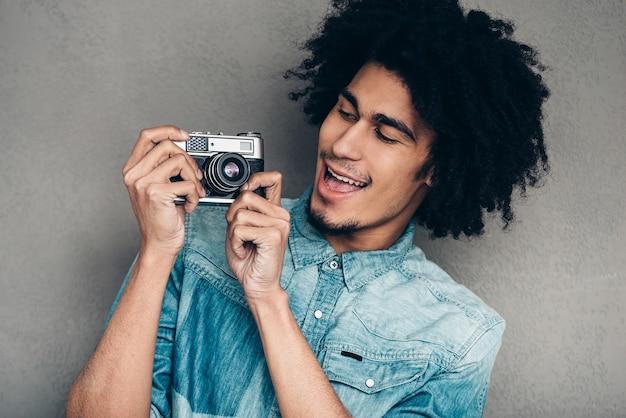 Das ding funktioniert einwandfrei! hübscher junger afrikanischer mann, der eine retro-kamera hält und sie anschaut
