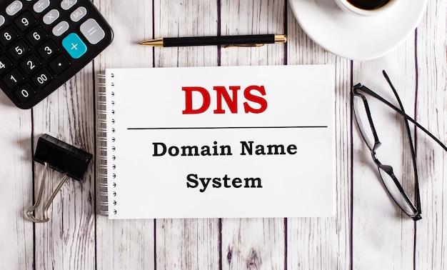 Das dns domain name system ist in einem weißen notizblock neben einem taschenrechner, kaffee, gläsern und einem stift geschrieben