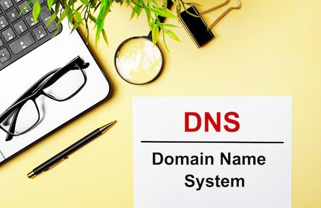 Das dns domain name system ist rot auf ein weißes stück papier auf einer hellgelben oberfläche neben einem laptop, einem stift, einer lupe, einer brille und einer grünen pflanze geschrieben