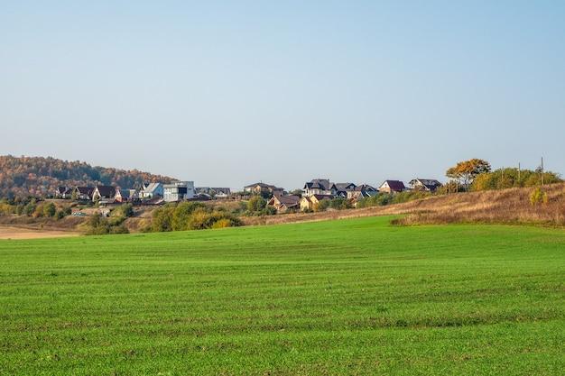 Das dorf in der grünen mulde. modernes bauerndorf in einer grünen wiese. russland.