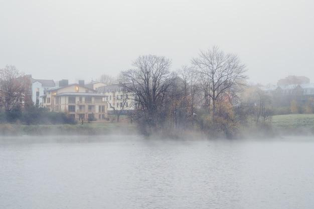 Das dorf liegt im nebel. morgendunst über der oberfläche des sees nahe gatchina stadt, russland.