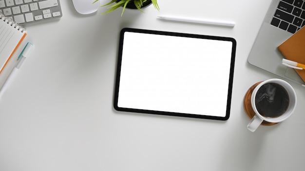 Das draufsichtbild des weißen arbeitsbereichs ist von einem weißen tablett mit leerem bildschirm und verschiedenen geräten umgeben.