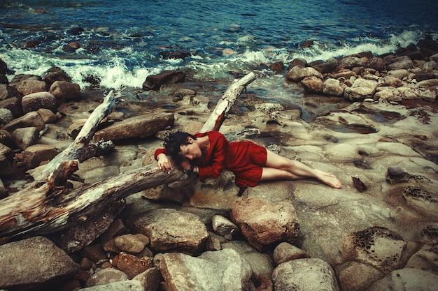 Das dunkelhaarige model posiert in einem roten kleid am seeufer