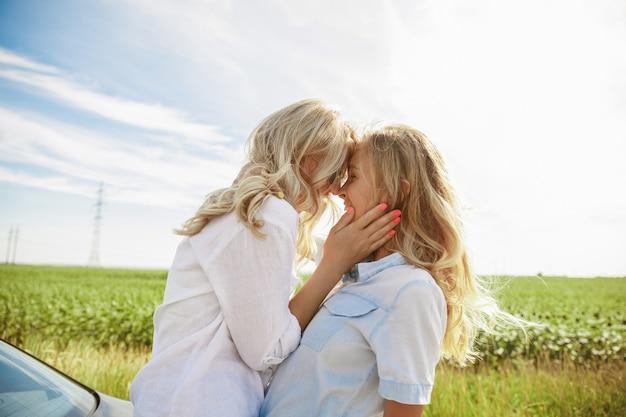 Das ehepaar der jungen lesbe hat auf dem weg zur ruhe das auto kaputt gemacht. küssen und kuscheln am kofferraum des autos. beziehung, probleme auf der straße, urlaub, ferien, flitterwochen-konzept.