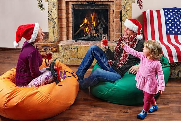 Das ehepaar in weihnachtsmützen sitzt auf einem sitzsack und trinkt wein mit seiner kleinen tochter in ihrer nähe.