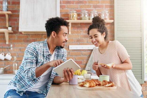 Das ehepaar mit gemischten rassen verbringt den samstagmorgen in der küche, macht snacks und benutzt einen tablet-computer