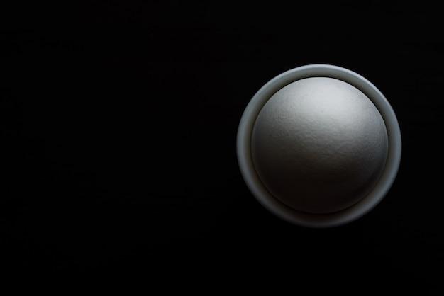 Das ei im ständer auf schwarzem hintergrund, ansicht von oben