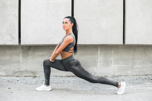 Das eignungsschönheitsmodell in der stilvollen kleidung, die das ausdehnen von muskeln tut, trainiert auf stadtstraßen. sportliches modemädchen in den gamaschen bildet draußen aus.