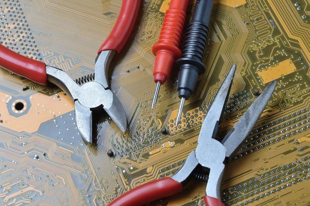 Das elektronik-reparaturwerkzeug liegt auf dem motherboard des computers. nahansicht.