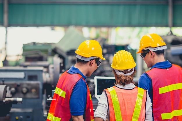 Das engineer team mix race arbeitet in der schwerindustrie mit der diskussion über laptops zusammen. schließen sie sich der engineer teamwork an.