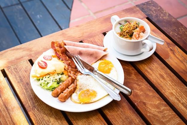 Das englische frühstück besteht aus spiegeleiern, speck, wurst und grünem salat