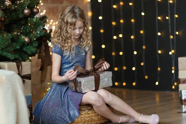 Das entzückende 10-jährige mädchen im herrlichen kleid hält geschenkbox, die nahe weihnachtsbaumöffnungsgeschenk sitzt.