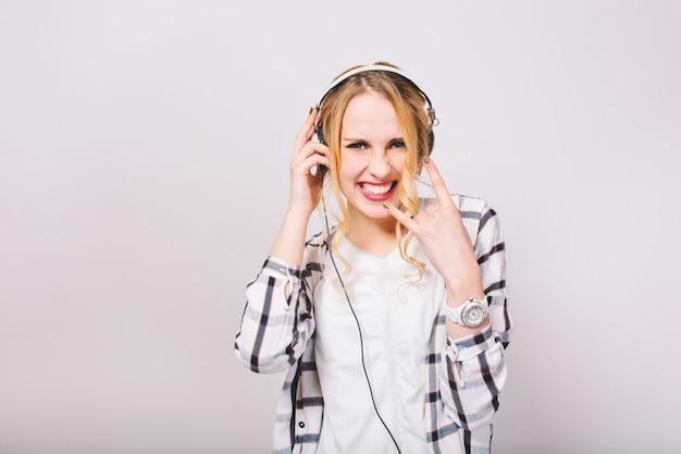 Das entzückende blonde mädchen im weißen trikot lächelt trotzig, hört rockmusik und hat spaß. stilvolle junge frau in kopfhörern, die trendige armbanduhr tragen, zeigt schwermetallschild und tanz.