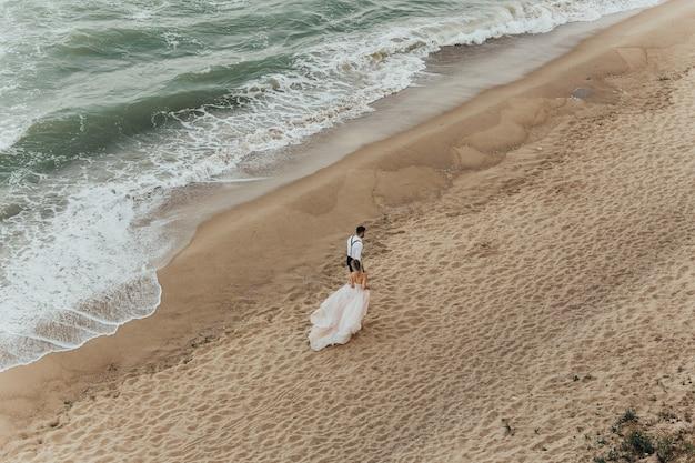 Das entzückende hochzeitspaar hält sich die hände, die am strand entlang gegen die meereswellen gehen.