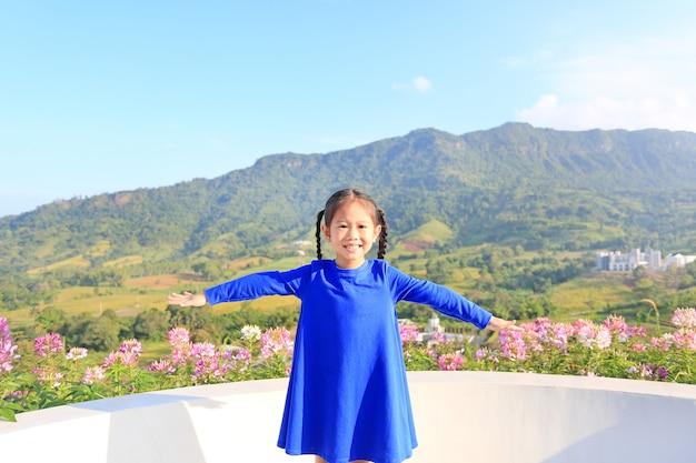 Das entzückende kleine asiatische kindermädchen, das frei mit den breiten armen sich fühlt, öffnen sich an den schönen bäumen und an den bergen auf blauem himmel.