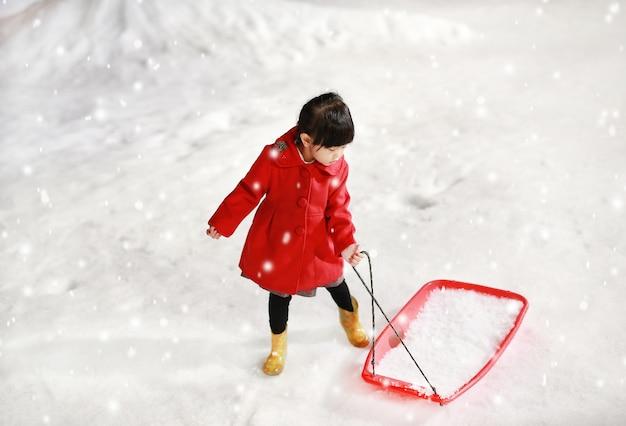 Das entzückende kleine mädchen, das eine rote jacke trägt, hat einen spaß im schnee