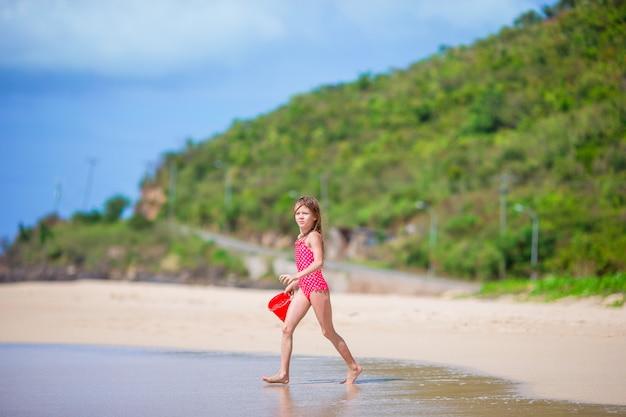 Das entzückende kleine mädchen, das mit strand spielt, spielt auf weißem tropial strand