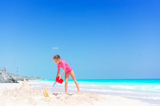 Das entzückende kleine mädchen, das mit strand spielt, spielt im seichten wasser