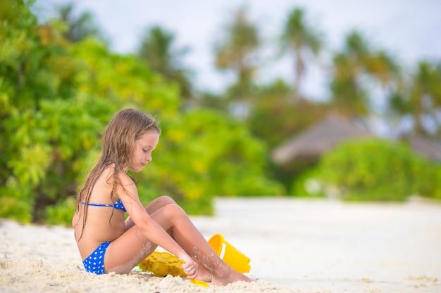 Das entzückende kleine mädchen, das mit strand spielt, spielt während der tropischen ferien