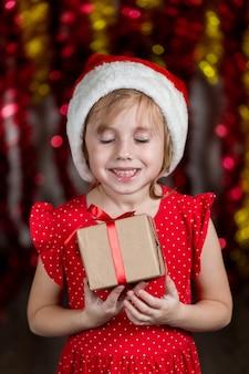 Das entzückende kleine mädchen in der weihnachtsmütze hält neujahrsgeschenk mit träumendem gesichtsausdruck.