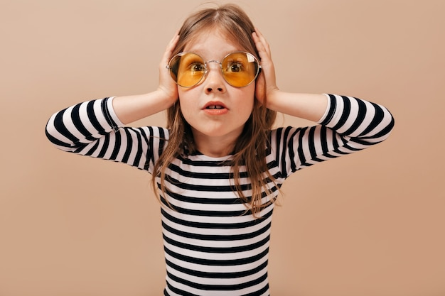 Das entzückende kleine süße mädchen, das runde gelbe brille trägt, sieht besorgt aus, hält hände auf dem kopf und schaut weg