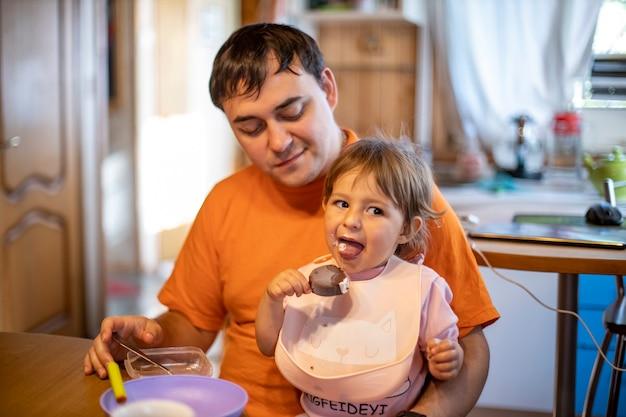 Das entzückende kleinkind isst gerne eis am stiel auf dem schoß der eltern in der inneneinrichtung