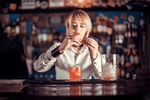 Das erfahrene barkeeper-mädchen formuliert einen cocktail, während es in der nähe der bartheke in der bar steht