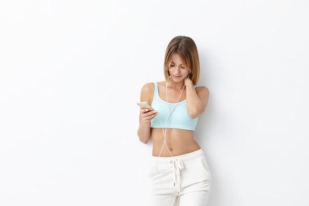 Das erholsame weibliche model trägt sportkleidung, hört lieblingsmusik über kopfhörer und smartphones